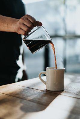man som häller upp svart kaffe från kanna